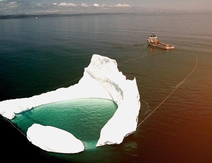 Ship towing an iceberg off the shore of Newfoundland / Canada ,